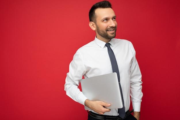Bel uomo brunet tenendo il computer portatile che guarda al lato in camicia bianca e cravatta su sfondo rosso isolato.