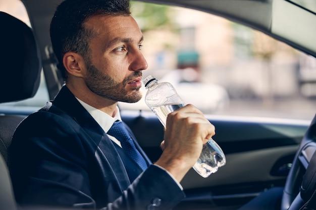 Un bell'uomo d'affari brunetta immerso nei suoi pensieri mentre si prepara per l'incontro