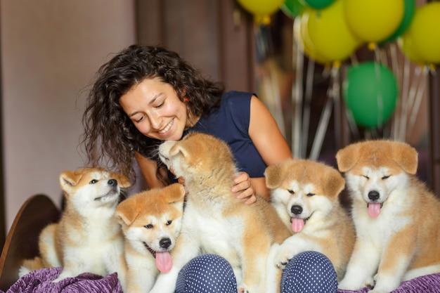 Bella ragazza bruna divertirsi abbracci e giocare con i cuccioli di akita inu