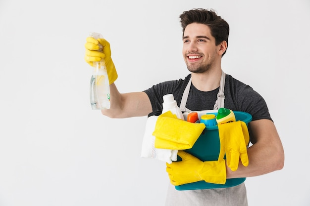 Bel casalingo bruna che indossa un grembiule in piedi isolato su bianco, con in mano un secchio pieno di detersivi