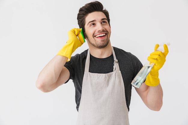Un bell'uomo di casa bruna che indossa un grembiule in piedi isolato su bianco, finge di parlare al telefono cellulare con una spugna