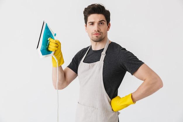 Bel brunetta domestico che indossa un grembiule in piedi isolato su bianco, mostrando ferro
