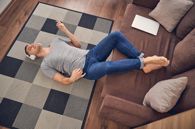 Bell'uomo bruna sdraiato su un tappeto colorato e rilassante ascoltando musica in cuffia
