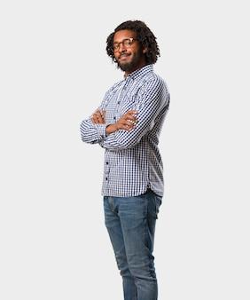 Uomo afroamericano bello di affari che attraversa le sue armi, sorridenti e felici