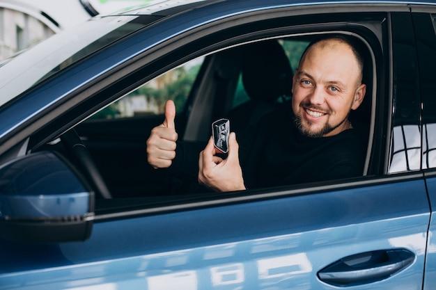 Uomo d'affari bello che sceglie un'auto in uno showroom di auto