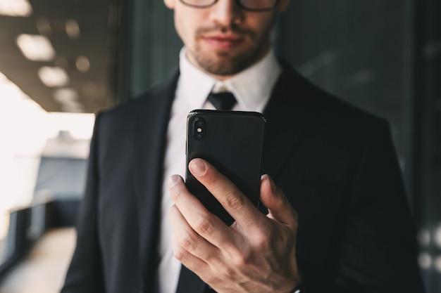 Uomo d'affari bello vicino al centro business utilizzando il telefono cellulare.