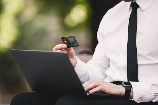 Uomo d'affari bello all'aperto nel parco utilizzando il computer portatile in possesso di carta di credito.