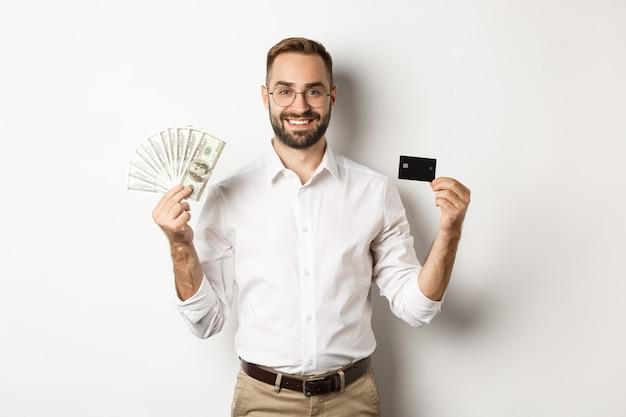 Uomo d'affari bello che mostra carta di credito e denaro dollari, sorridendo soddisfatto, in piedi su sfondo bianco.