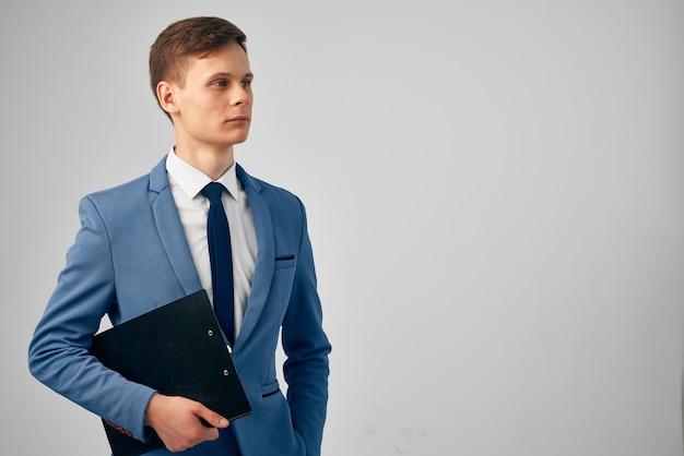 Bell'uomo d'affari in giacca e cravatta con documenti nelle mani del manager dello studio