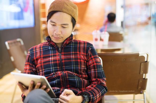 Bell'uomo d'affari in una tavoletta utilizzando felice nella caffetteria. uomo asiatico