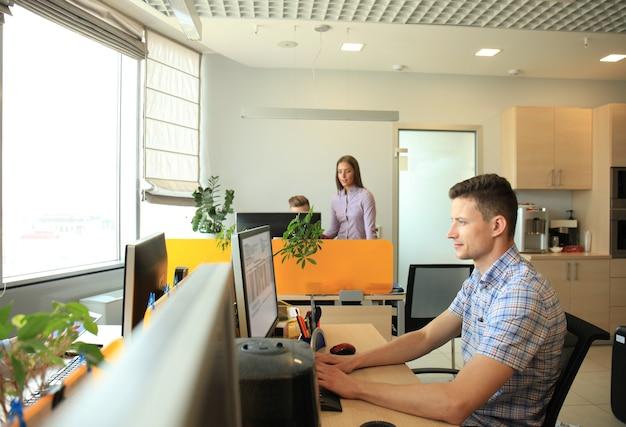Bell'uomo d'affari in abbigliamento casual sullo sfondo dei suoi partner nell'ufficio creativo