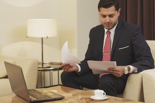 Uomo d'affari bello che fa un certo lavoro di ufficio e che per mezzo del suo computer portatile