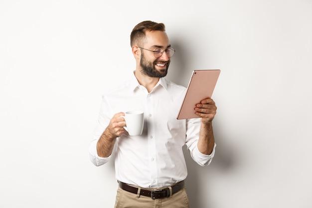 Bello imprenditore bere caffè e leggere sulla tavoletta digitale, sorridendo soddisfatto, in piedi su sfondo bianco.