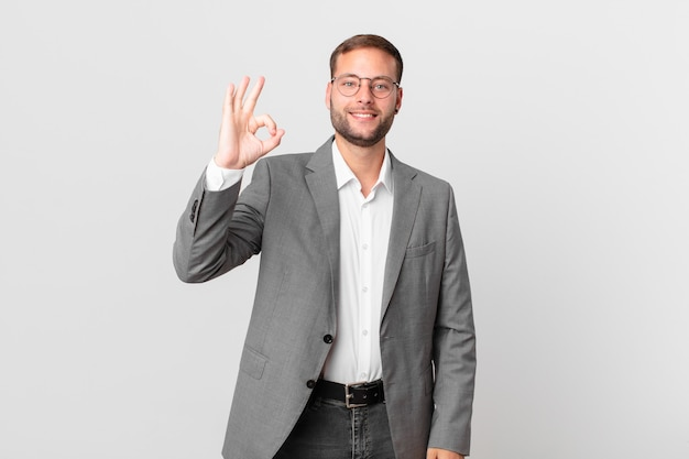 Un bell'uomo d'affari che si sente felice, mostra approvazione con un gesto ok