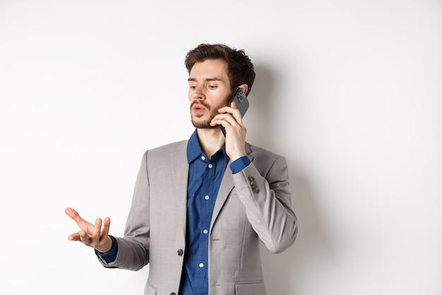 Uomo d'affari bello che ha chiamata di affari sul telefono, gesticolando mentre parla sul cellulare, conversazione, sfondo bianco.