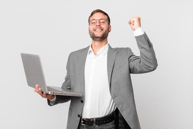 Bell'uomo d'affari che tiene un laptop