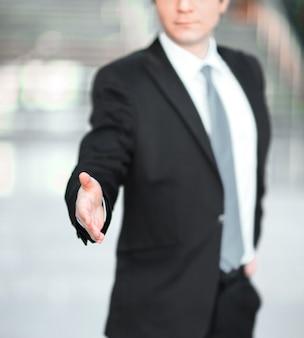 Un bell'uomo d'affari che tende la mano per una stretta di mano.il concetto di partnership