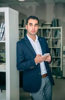 Uomo d'affari bello che tiene smartphone appoggiato su una libreria nella sede centrale a
