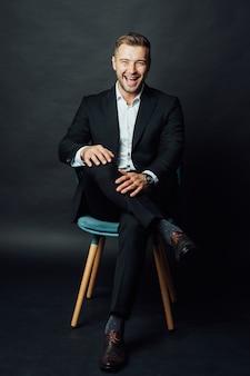 Uomo d'affari bello con vestito si siede su una sedia in uno studio fotografico.