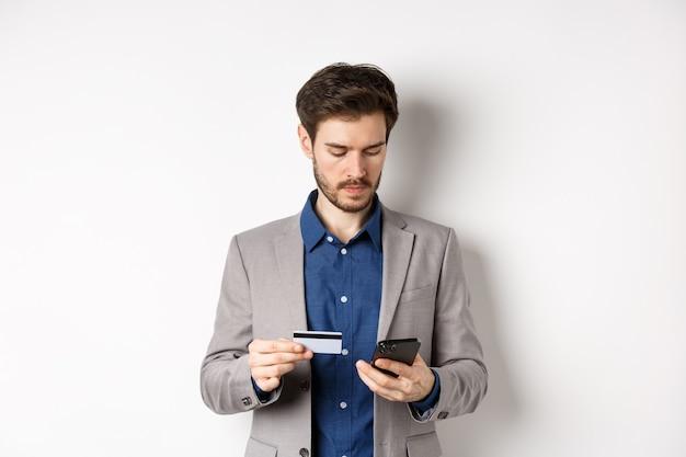 Bello imprenditore pagando online con carta di credito e smartphone, in piedi su sfondo bianco in tuta.