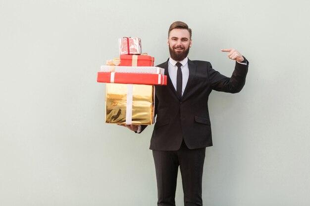 Bell'uomo d'affari che punta le scatole regalo con il dito e guarda la telecamera