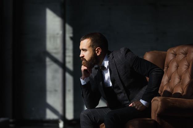 Bello imprenditore in posa seduta sul divano in interni