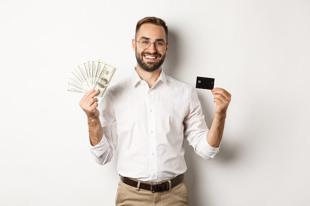 Uomo d'affari bello che mostra carta di credito e dollari di denaro, sorridendo soddisfatto, in piedi su sfondo bianco.