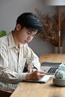 Bello uomo d'affari seduto nella sua stanza dell'ufficio e prendere appunti sul taccuino.