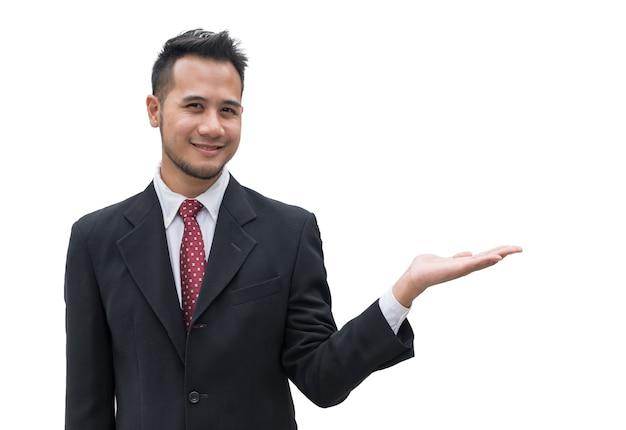 Uomo d'affari bello che sorride con il palmo della mano che mostra qualcosa