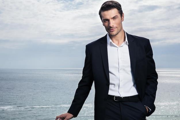 Bello imprenditore in piedi all'aperto con il mare sulla parete