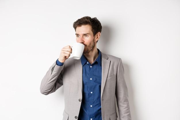 Uomo d'affari bello in vestito che beve caffè o tè dalla tazza dell'ufficio, guardando da parte il logo, in piedi su sfondo bianco.