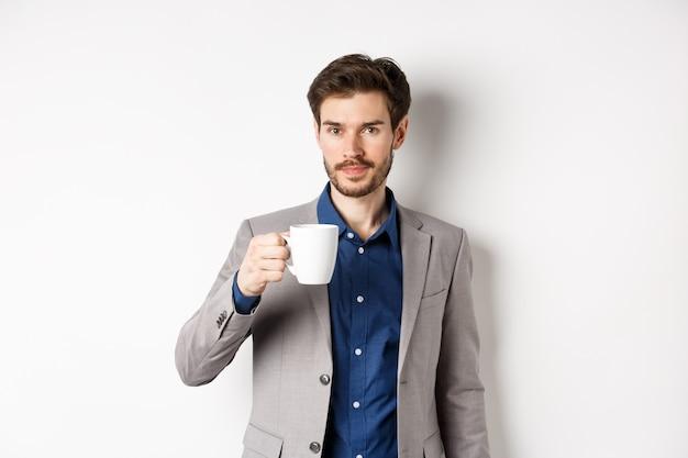 Uomo d'affari bello in vestito che beve caffè o tè dalla tazza dell'ufficio, levantesi in piedi contro il fondo bianco.