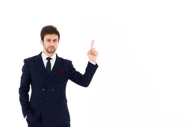 Uomo d'affari bello in giacca e cravatta che punta il dito con il muro bianco isolato.