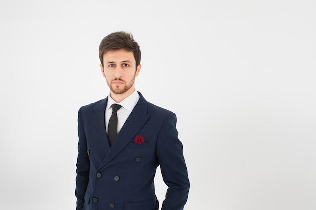 Uomo d'affari bello in giacca e cravatta con muro bianco isolato.