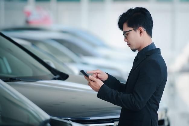 L'uomo d'affari bello in vestiti e vetri che parla sul telefono nell'ufficio si congratula con le vendite è stato completato per il nuovo showroom dell'automobile.