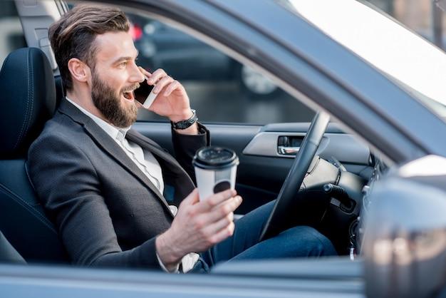 Un bell'uomo d'affari che parla con il telefono mentre guida un'auto in città