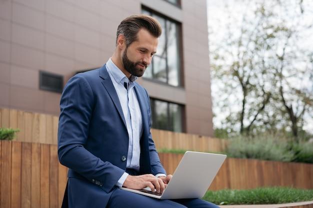 Un bell'uomo d'affari che utilizza un computer portatile per guardare corsi di formazione online che lavorano da casa