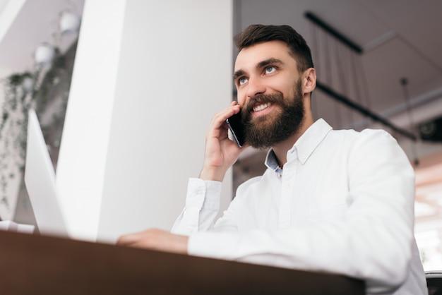 Uomo d'affari bello che per mezzo del computer portatile, parlando sul telefono cellulare, funzionante dalla casa