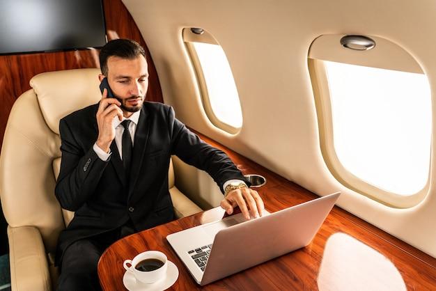 Uomo d'affari bello che porta vestito elegante che vola su un jet privato esclusivo