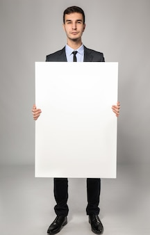 Bello uomo d'affari con cartellone pubblicitario vuoto su sfondo grigio