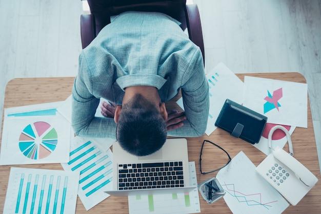 Uomo d'affari bello con una giacca blu che lavora in ufficio