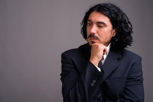Bello imprenditore con i baffi che indossa tuta contro il muro grigio