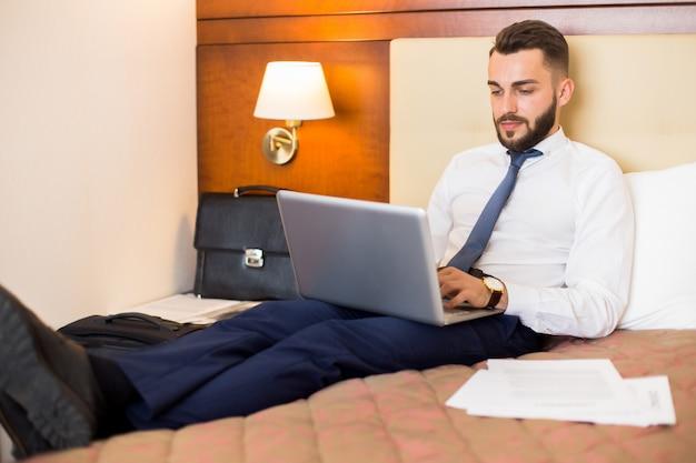 Uomo d'affari bello che lavora nella camera da letto