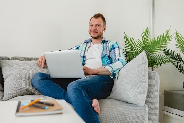 Bell'uomo impegnato e concentrato in camicia seduto rilassato sul divano di casa a tavola che lavora online sul laptop da casa