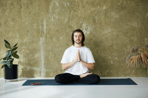 Bello calmo uomo seduto in lotus asana e namaste mudra, maschio in camicia bianca con calma emozione rilassata tenendo le braccia in namaste