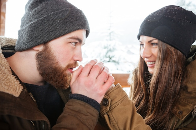 Bel giovane barbuto attento che scalda le mani della sua ragazza in inverno