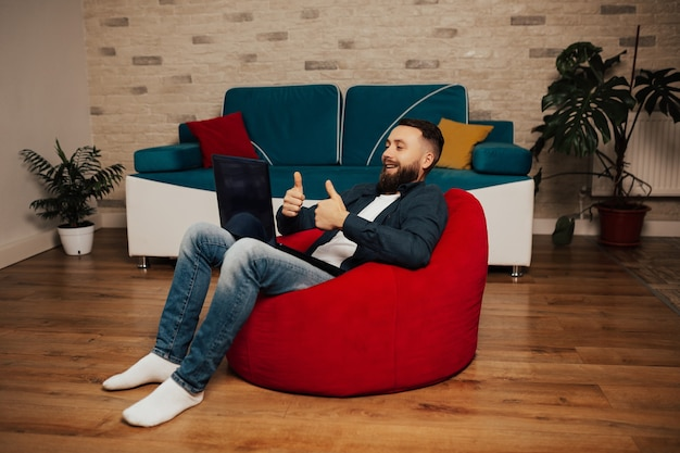 Uomo barbuto casuale bello che parla in linea. uomo adulto felice che ha una videochiamata con un laptop a casa.