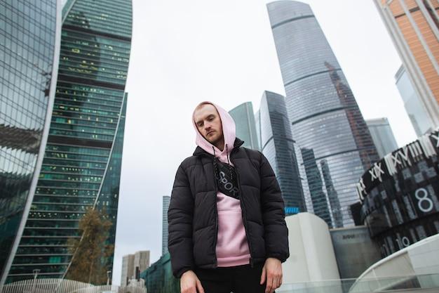 Bell'uomo casual in giacca nera e felpa con cappuccio rosa in piedi su una vista del grattacielo. città di mosca.