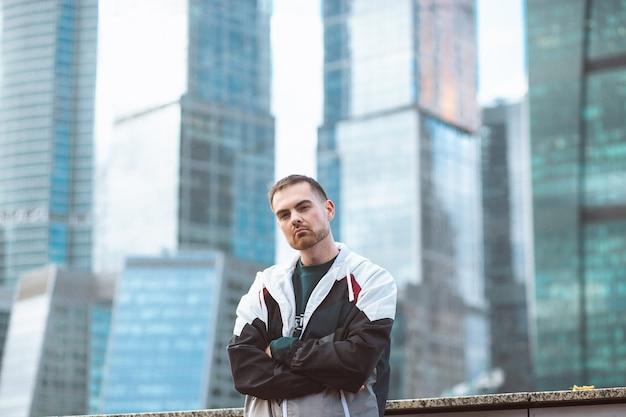 Bell'uomo casual in giacca a vento in piedi su una vista del grattacielo. stile sportivo e business.