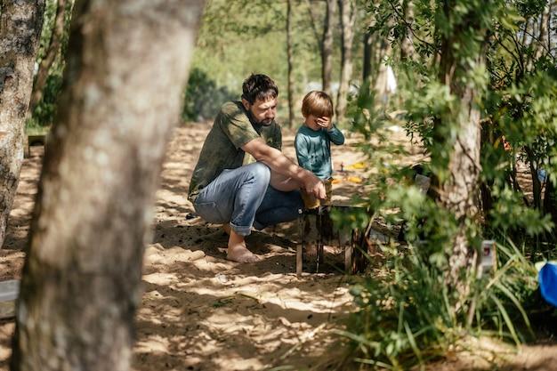 Bello uomo barbuto caucasico e suo figlio di 6 anni che arrostiscono la carne sul barbecue in campagna